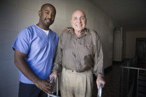caregiver and elderly man walking