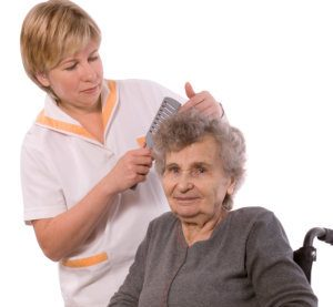 caregiver grooming an elderly woman's hair